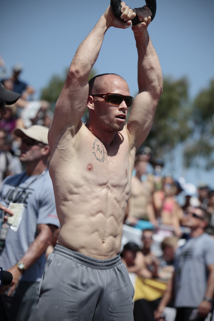Chris Spealler performing an exercise shirtless during a CrossFit event