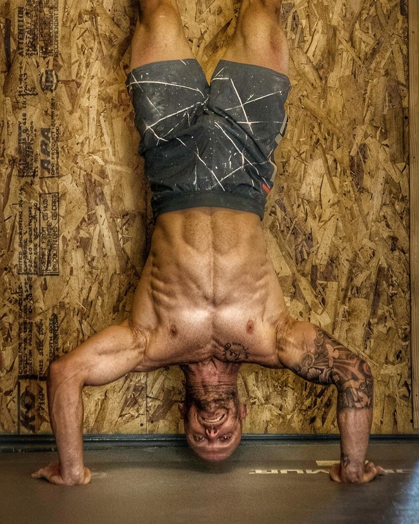 Chris Spealler doing a shirtless handstand looking ripped