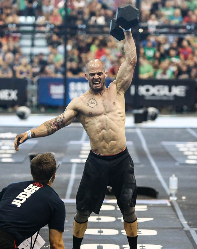 Chris Spealler lifting a dummbbell over his head during a CrossFit competition
