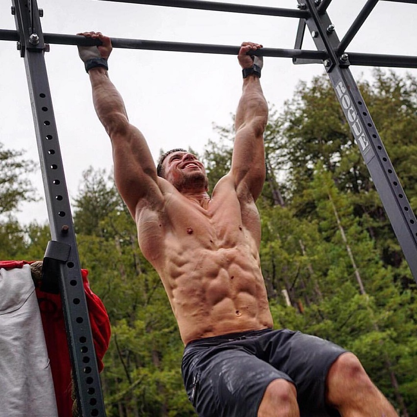 Dan Bailey performing pull ups shirtless, looking ripped