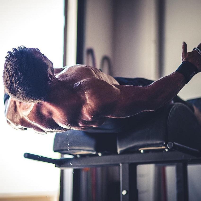 Dan Bailey exercising shirtless on a bench