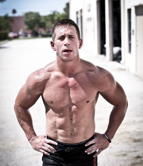 Dan Bailey standing shirtless outdoors in the sun, looking strong and lean