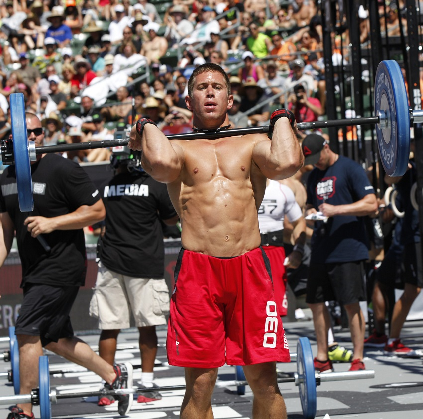 Dan Bailey lifting a heavy overhead press while being shirtless during a CrossFit competition