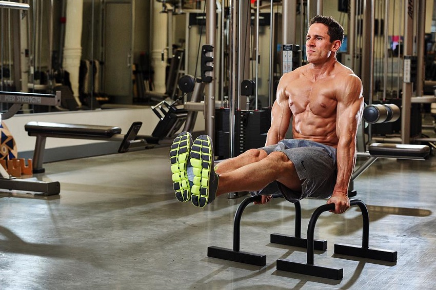 Don Saladino doing triceps dips with his legs raised up, working on his abs and triceps