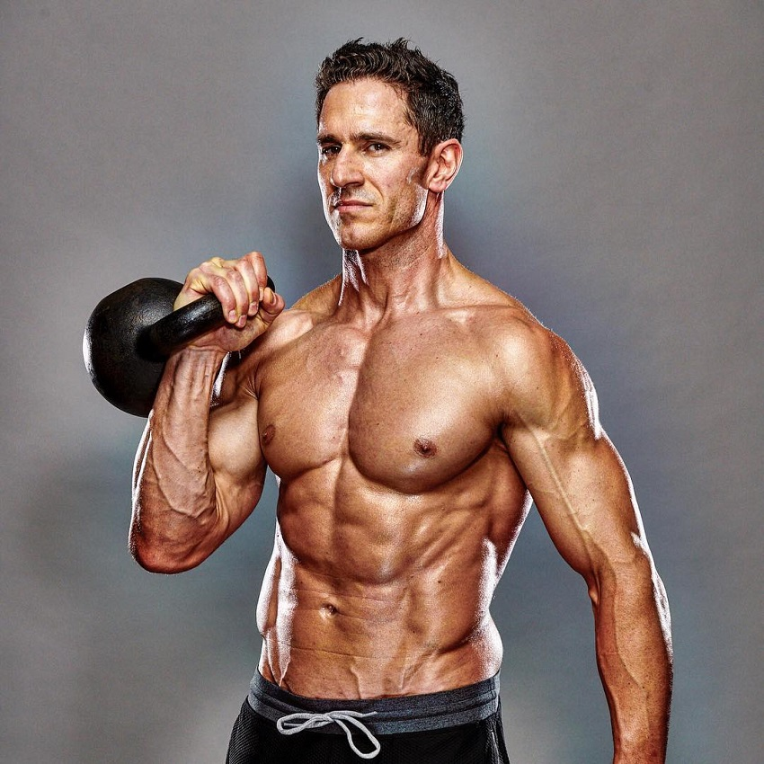 Don Saladino posing shirtless with a black kettlebell in his hand looking ripped and aesthetic