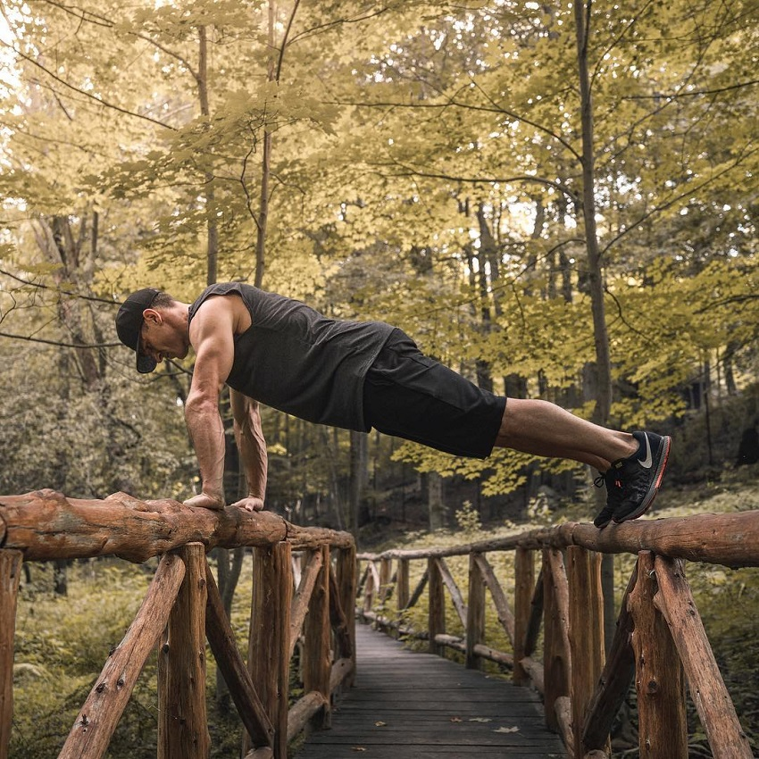 Don Saladino doing a push up on a wooden bridge looking fit