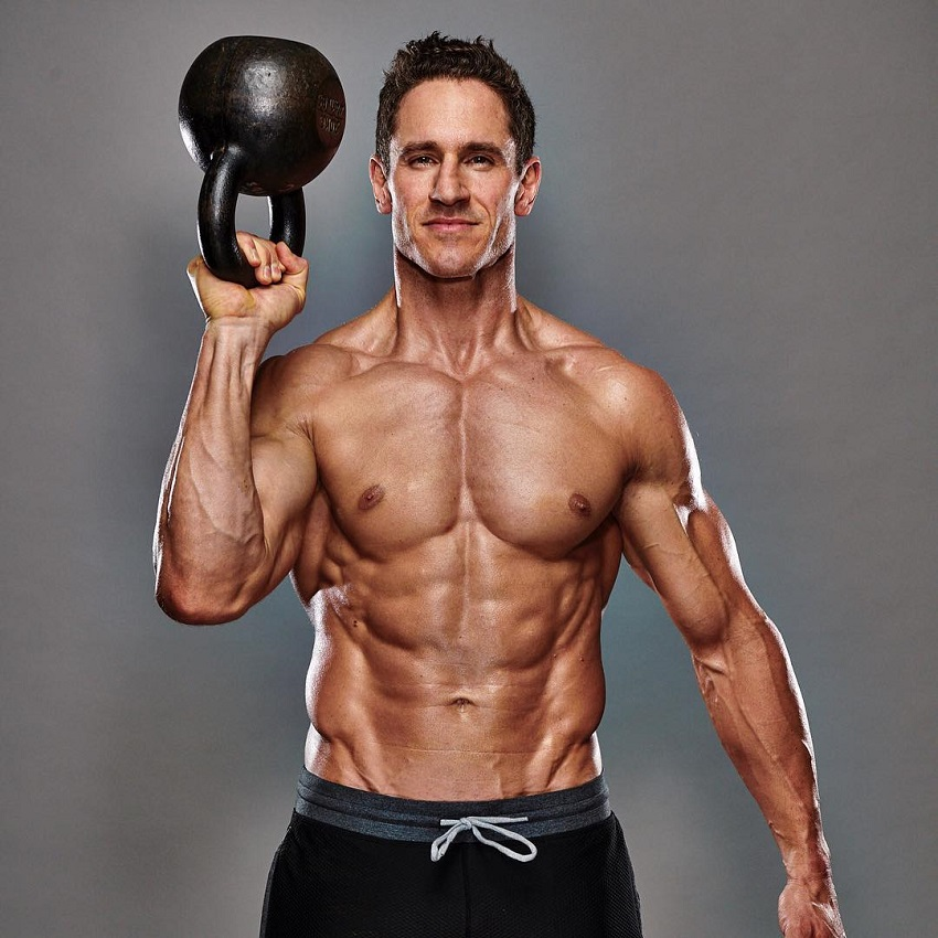 Don Saladino posing shirtless with a kettlebell in his hand looking strong and ripped