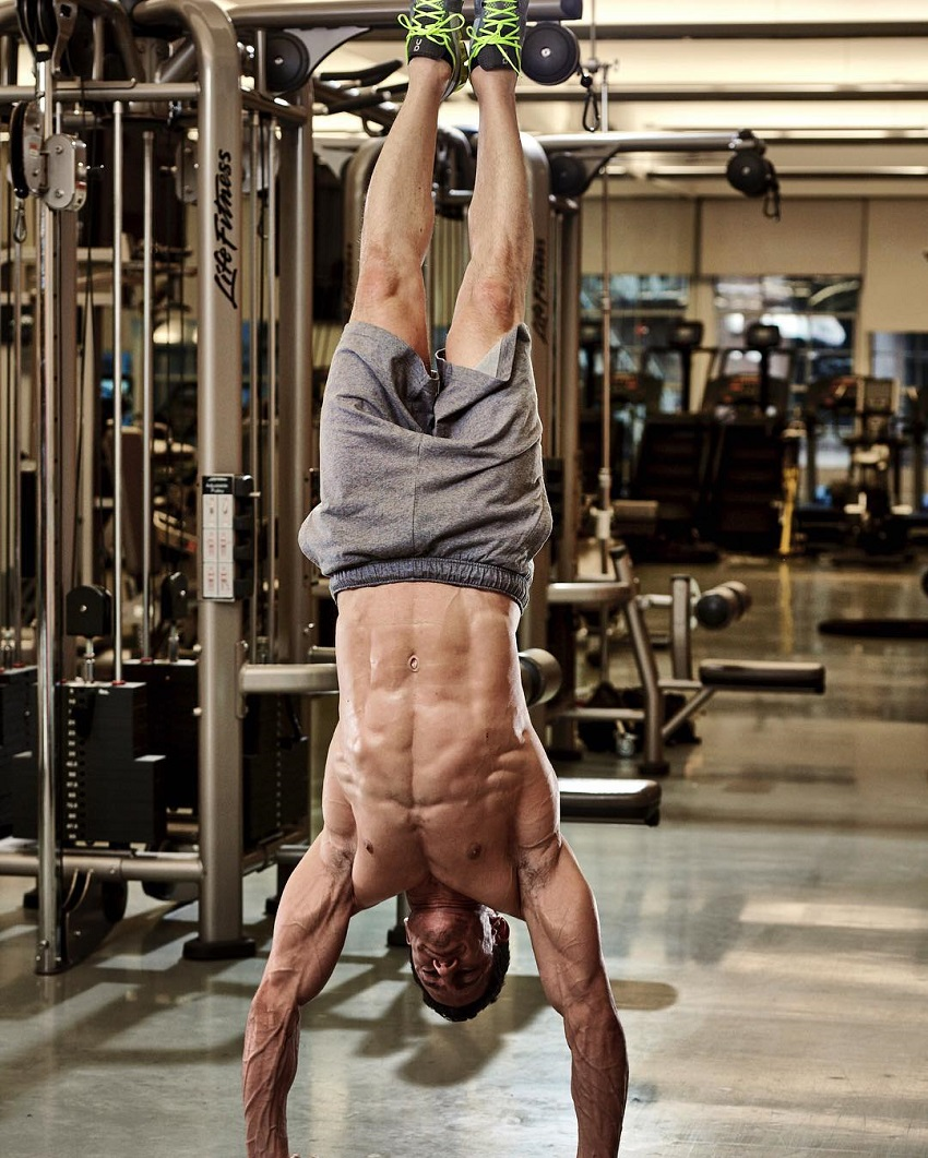 Don Saladino doing a shirtless handstand looking fit and riped