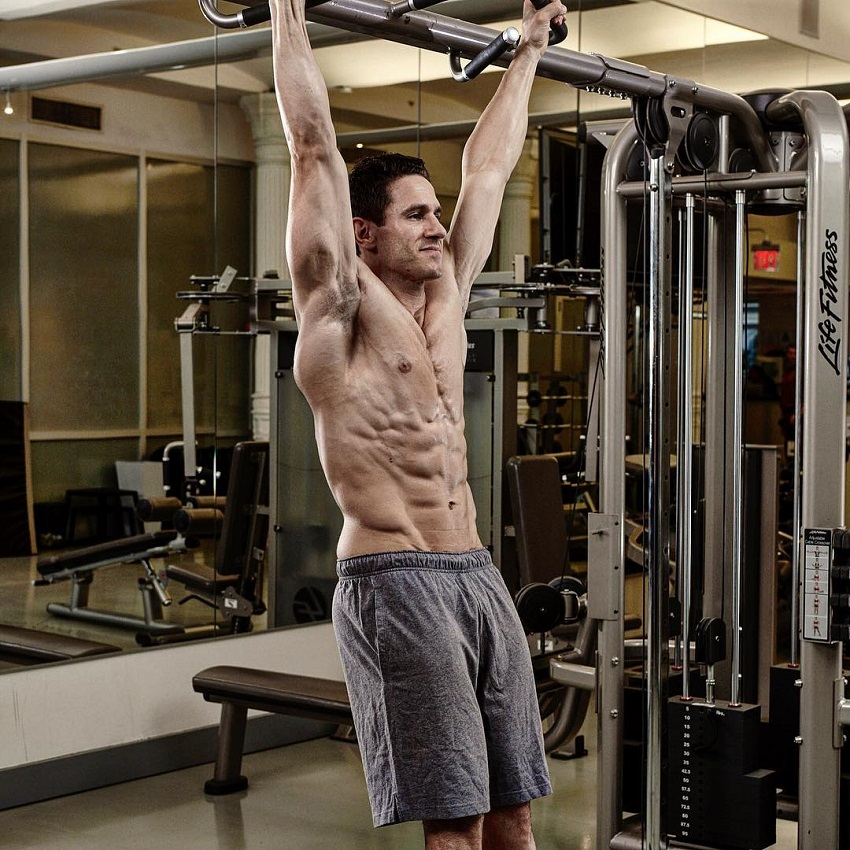 Don Saladino hanging on a pull up bar looking ripped without a shirt on