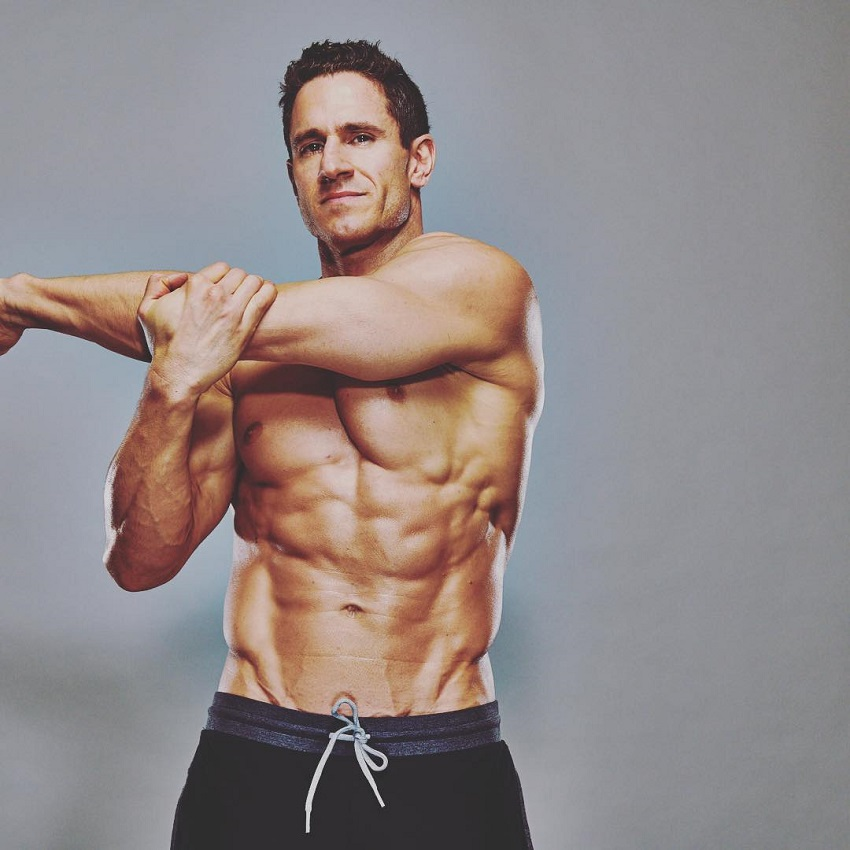 Don Saladino stretching his arms shirtless looking ripped
