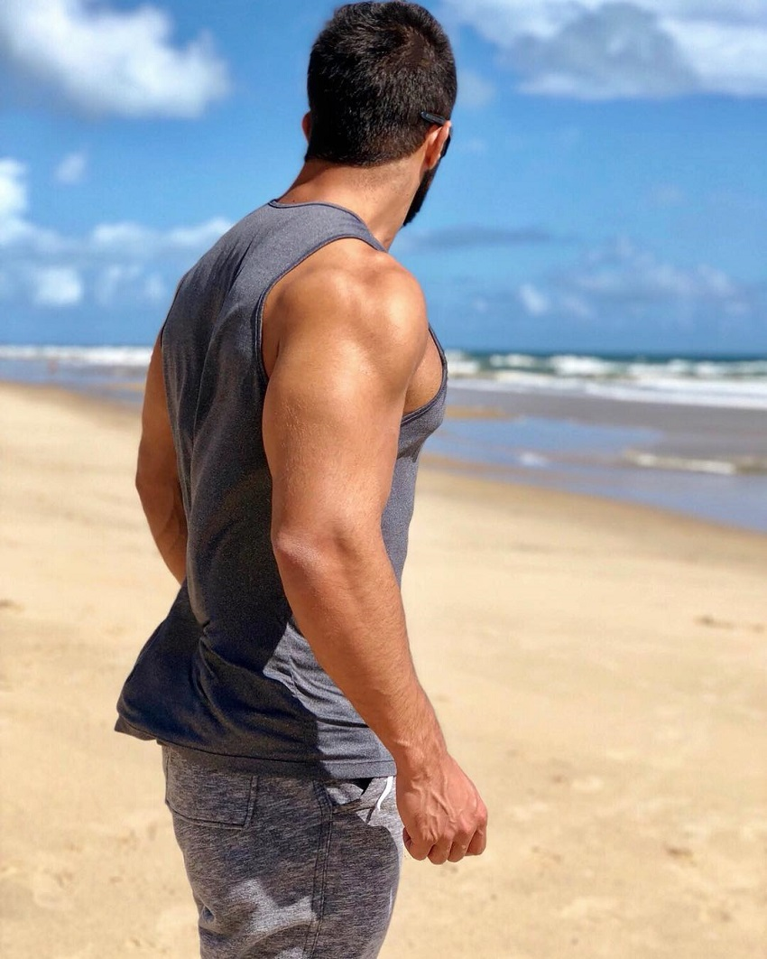 Jefferson Ferreira looking muscular and ripped in his tank top shirt on a beach