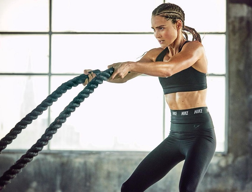Kirsty Godso performing battle ropes in her sportswear looking fit and lean