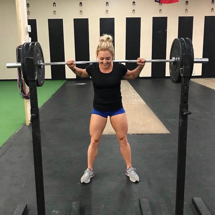 Kylee Nicole doing heavy squats with a barbell looking happy and fit