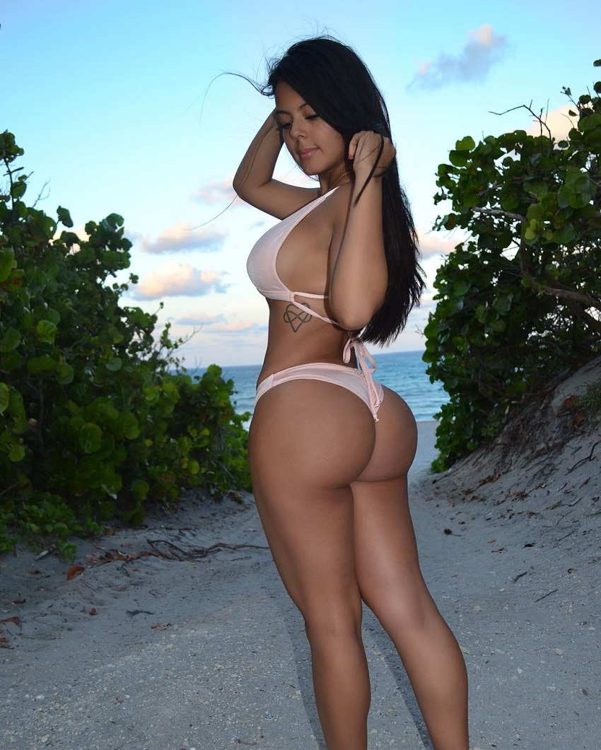 Nicole Borda posing by the sand beach looking curvy and fit