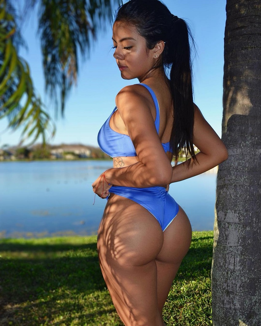 Nicole Borda posing by a palm tree showing off her curvy glutes