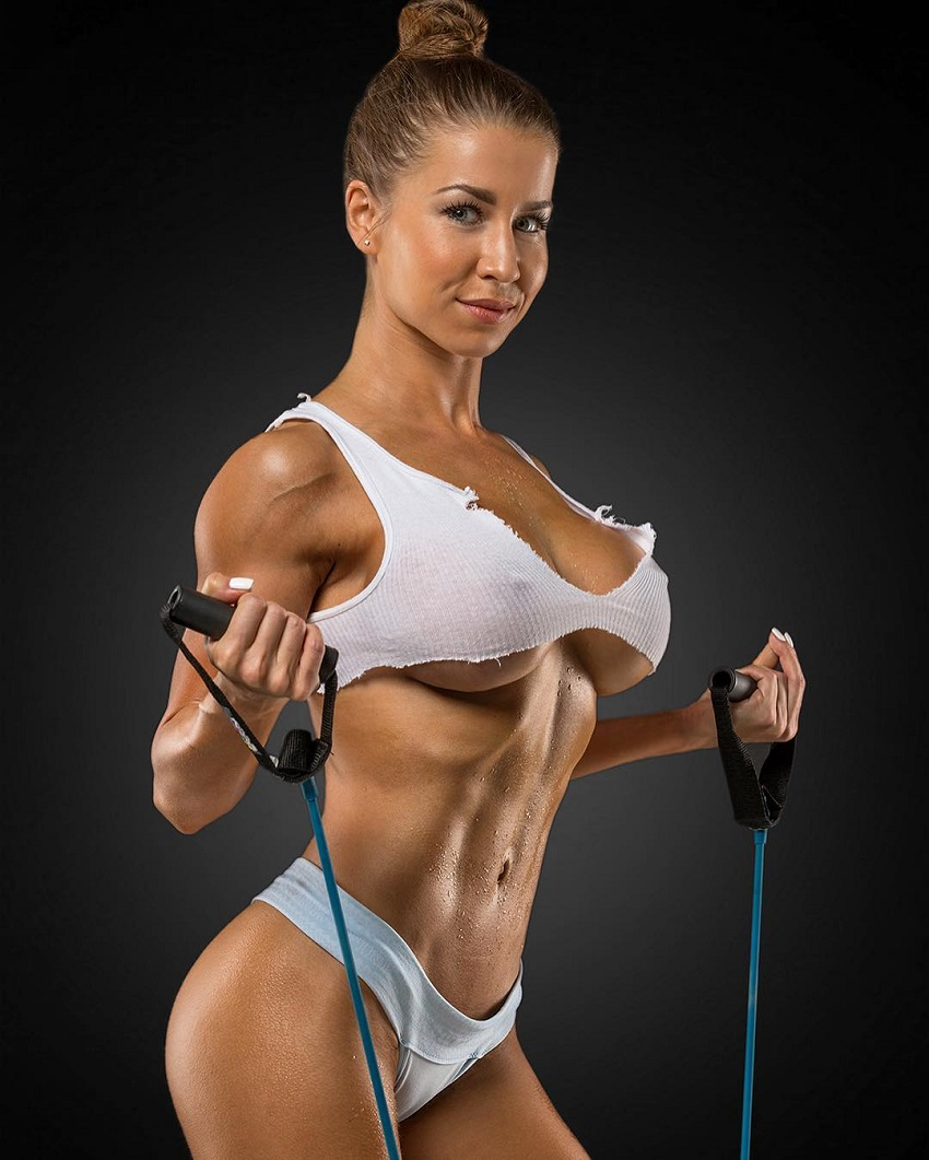 Nika Lazutina posing in a photo shoot working out with bands, looking ripped and busty