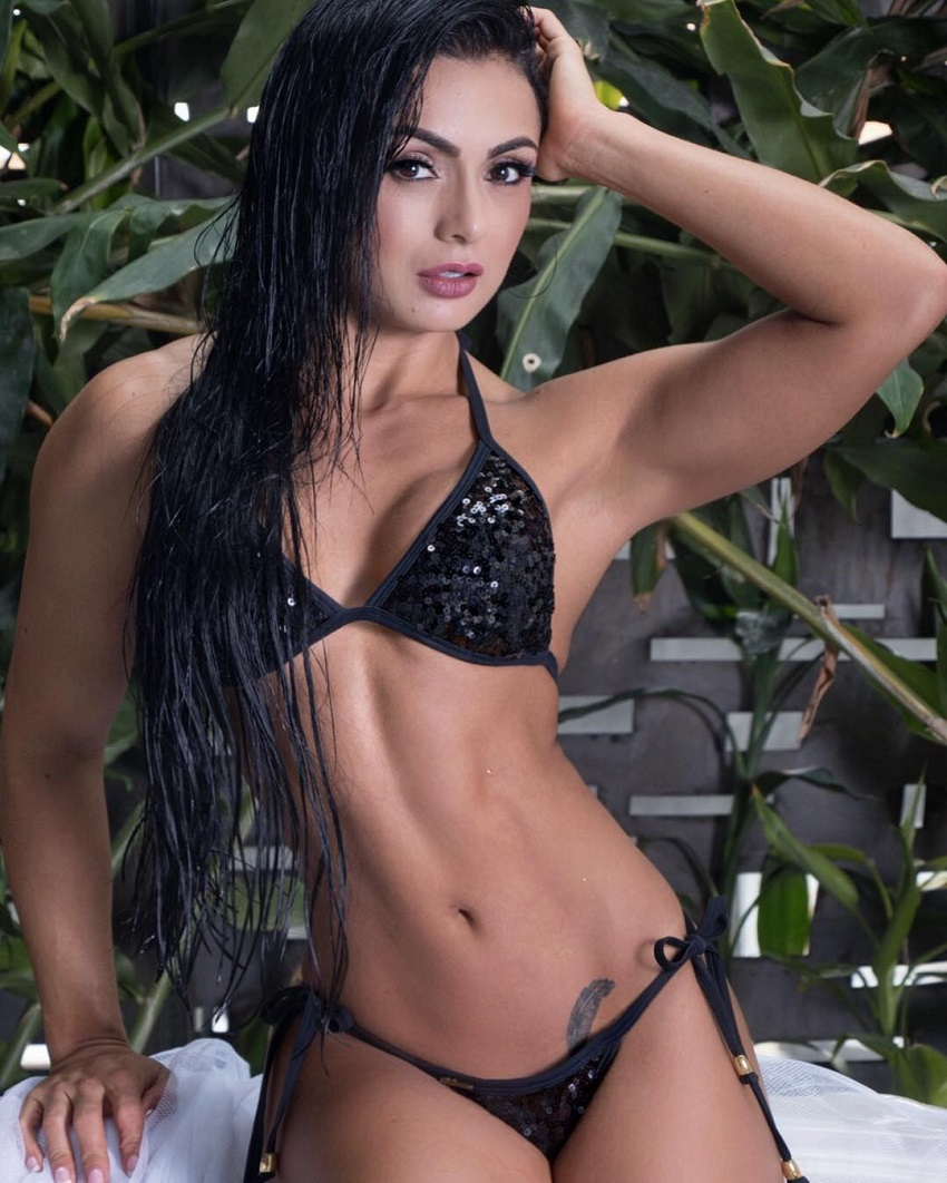 Paola Macias posing for a photo in a black bikini looking fit and lean