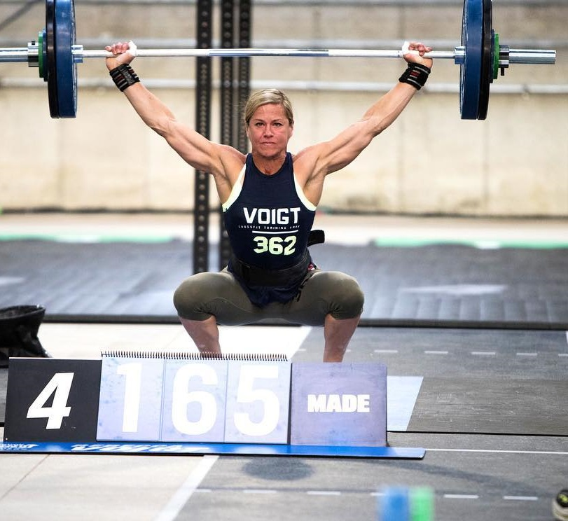 Rebecca Voigt Miller doing an overhead press with a barbell during a CrossFit contest