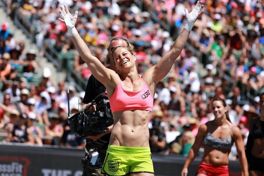 Rebecca Voigt Miller with her hands raised in the air during CrossFit competition