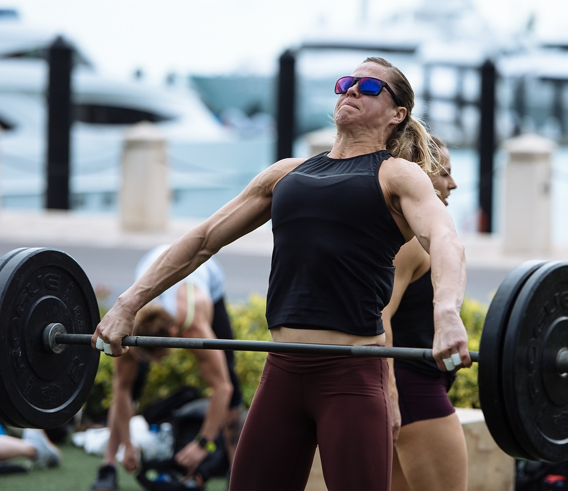 Rebecca Voigt Miller doing heavy barbell lifts during a CrossFit event