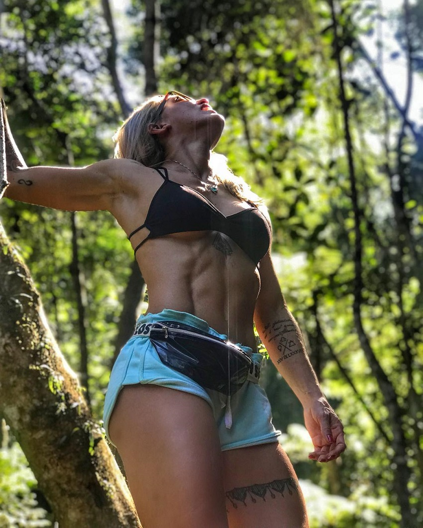 Roberta Mezencio looking up in the woods looking ripped and toned