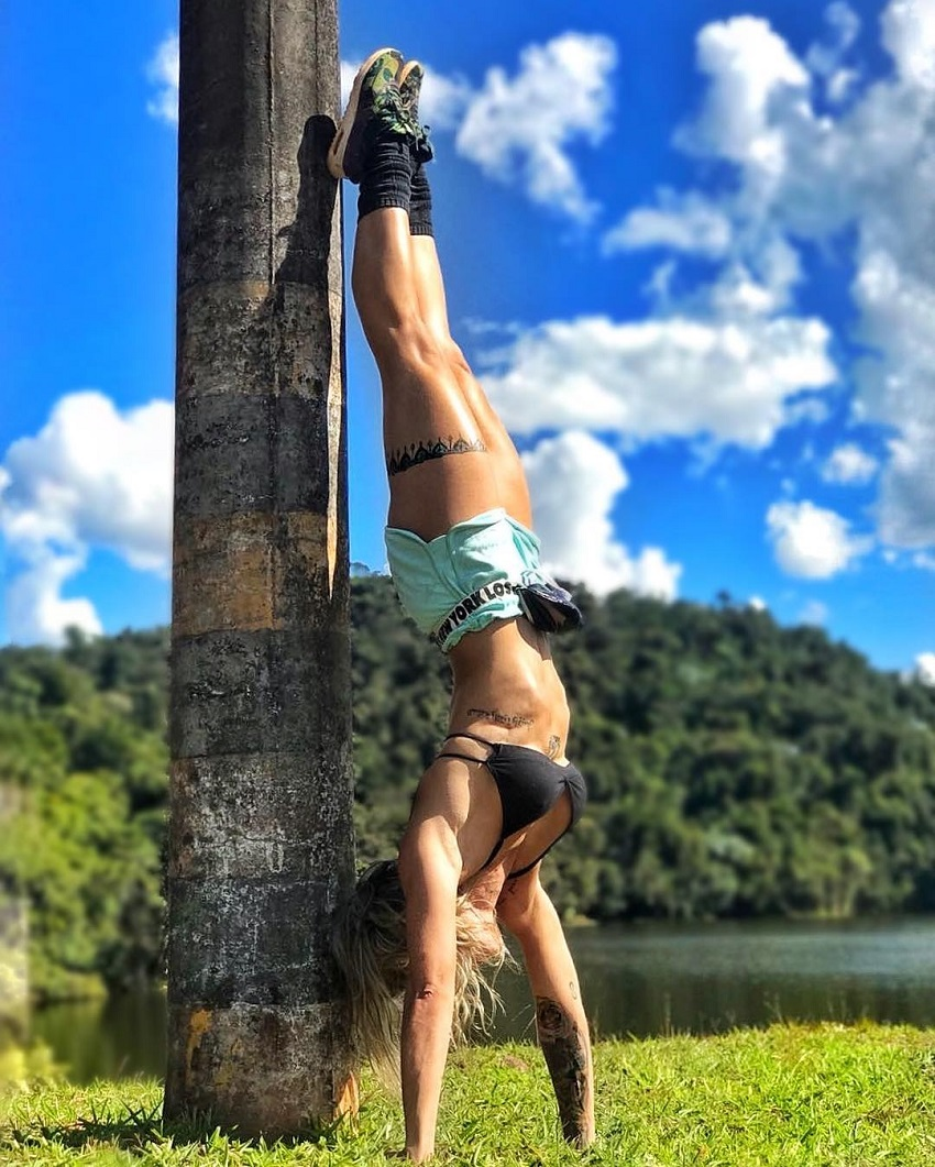 Roberta Mezencio doing a handstand in the nature looking lean and fit