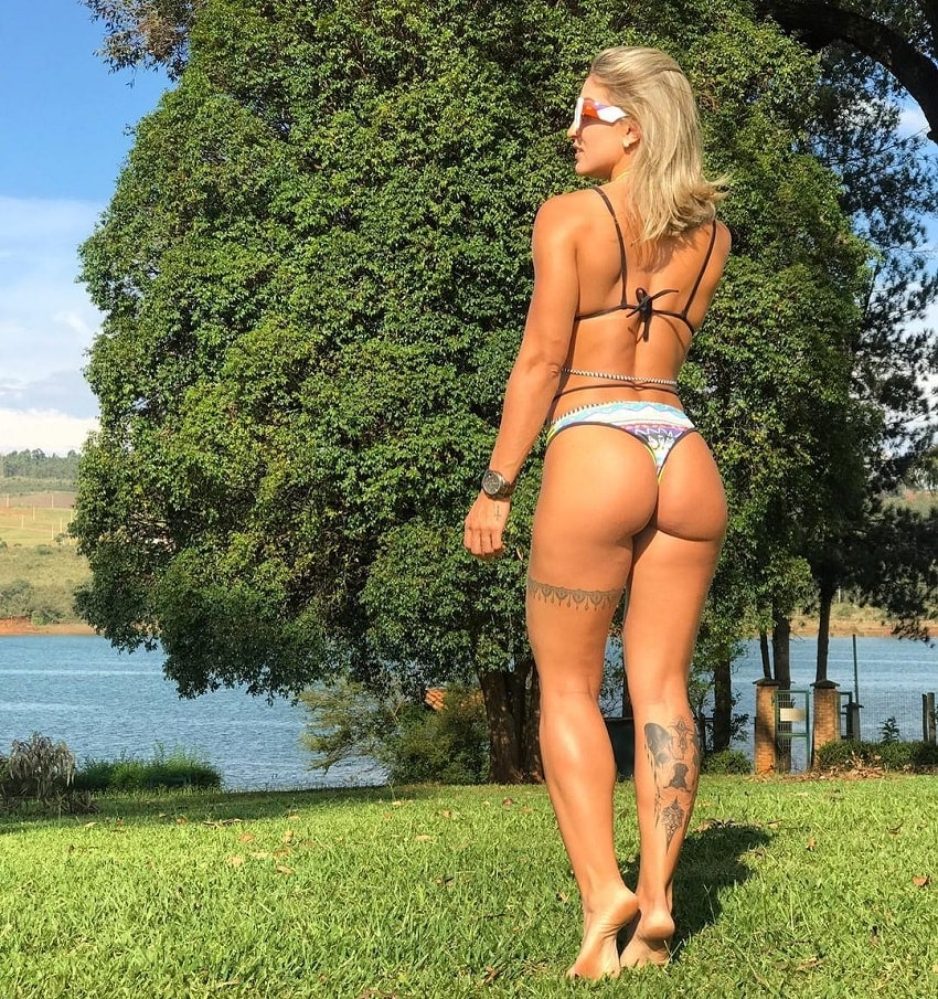 Roberta Mezencio walking down a park with a lake, looking fit and curvy