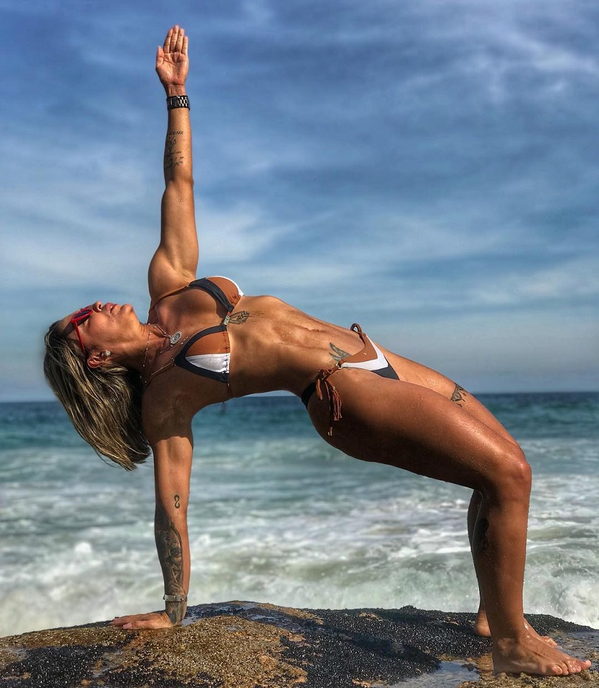 Roberta Mezencio leaning against the rock on the beach looking fit and lean