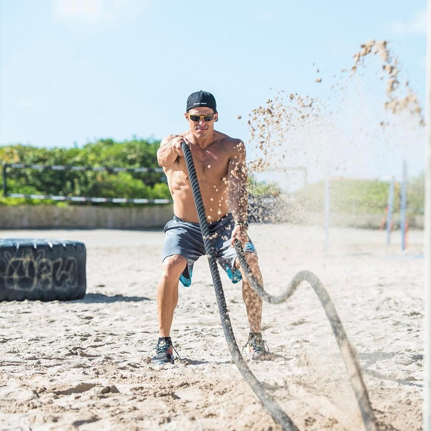 Shawn Ramirez performing battle ropes on the beach