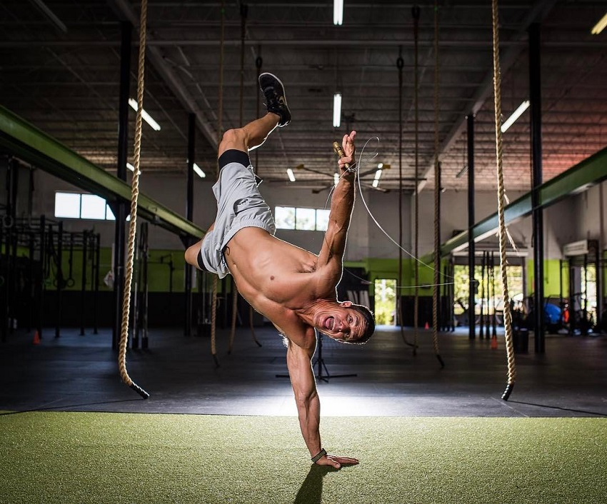 Shawn Ramirez doing a handstand while shirtless looking fit and strong