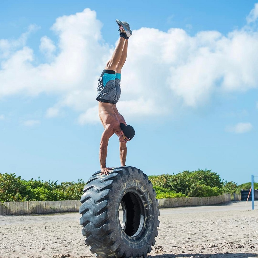 Shawn Ramirez doing a handstand on a big tire on the beach