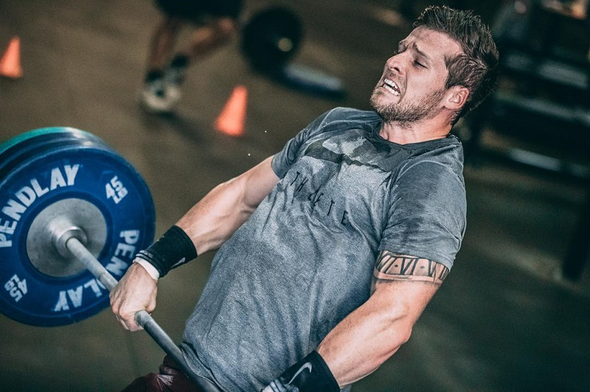 Travis Mayer lifting a heavy barbell looking fit and strong
