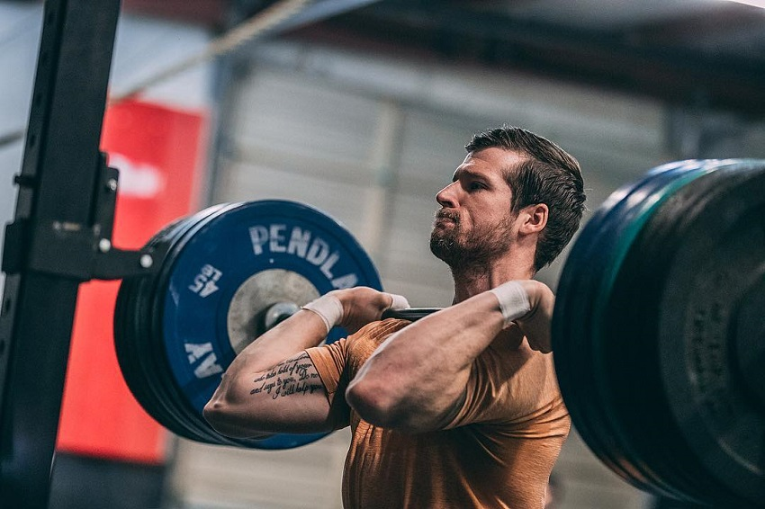 Travis Mayer lifting a barbell loaded with weights looking strong