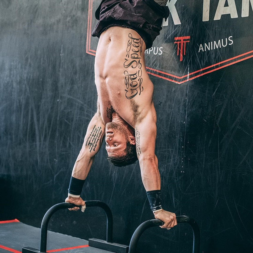 Travis Mayer doing a hand stand on bars looking fit and lean