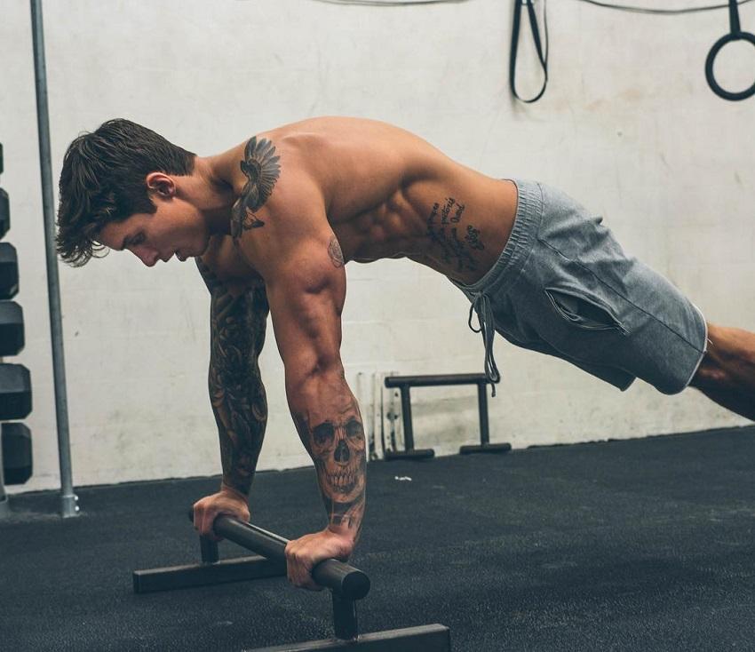 Adi Gillespie doing push ups in a gym while shirtless, showcasing his bulging triceps