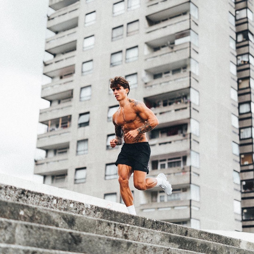 Adi Gillespie running shirtless on top of a building