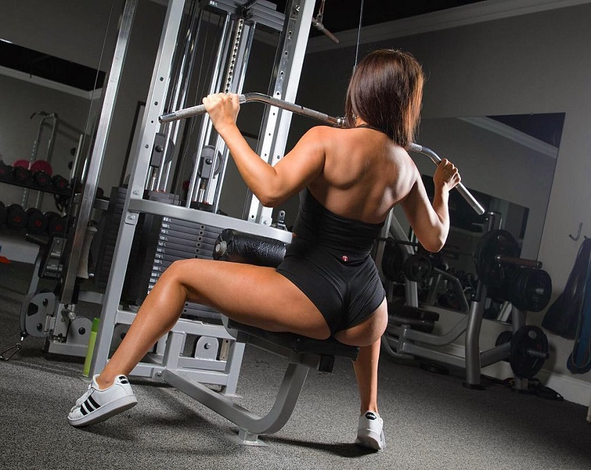 Amanda Hagan doing machine lat pull-downs in a gym