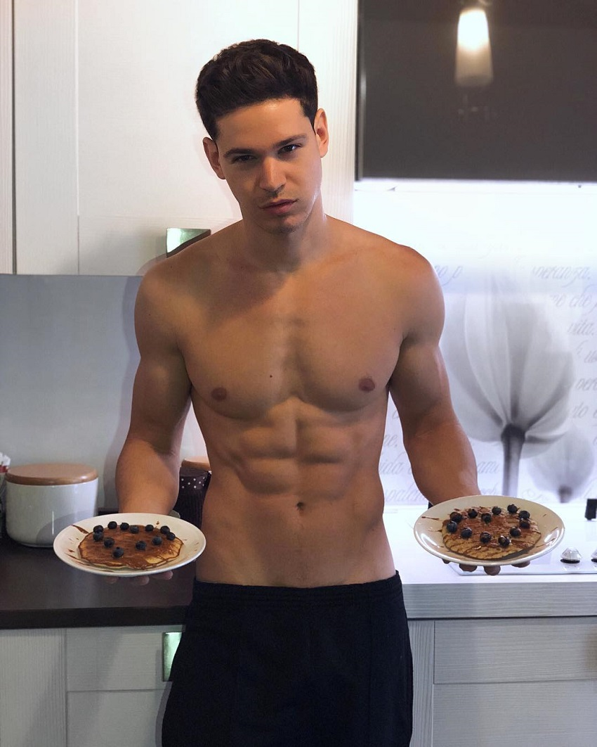 Andrea Moscon posing shirtless with two plates in his hands looking ripped