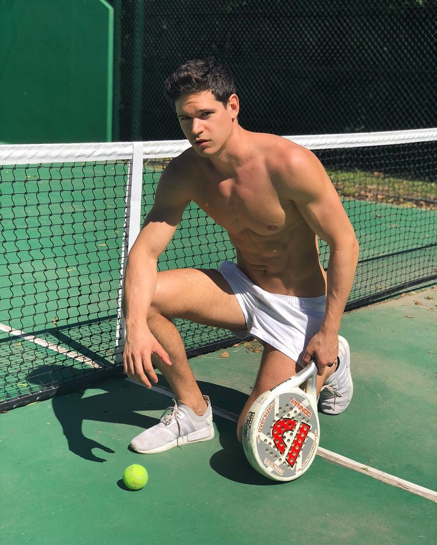 Andrea Moscon posing by a tennis court looking ripped