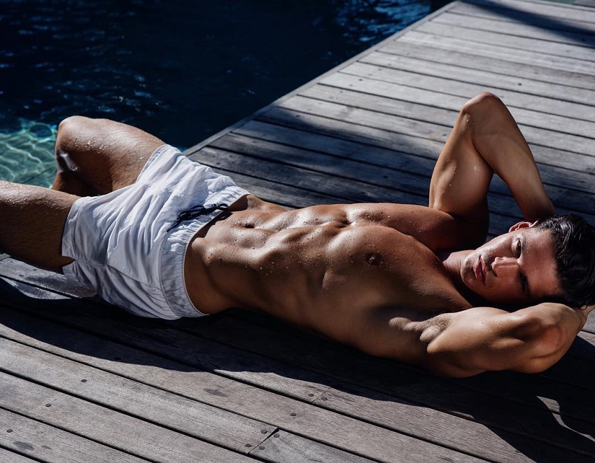 Andrea Moscon lying shirtless on a wooden bridge, looking ripped