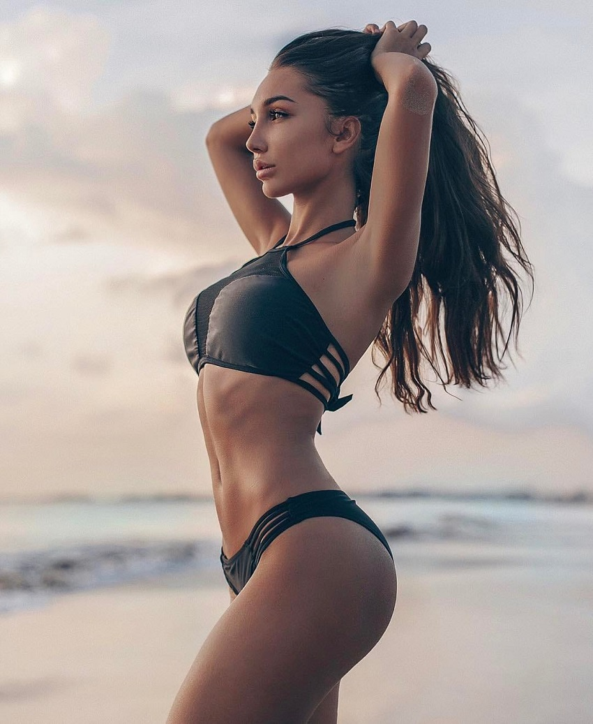 Anyuta Rai standing on the beach looking fit and lean
