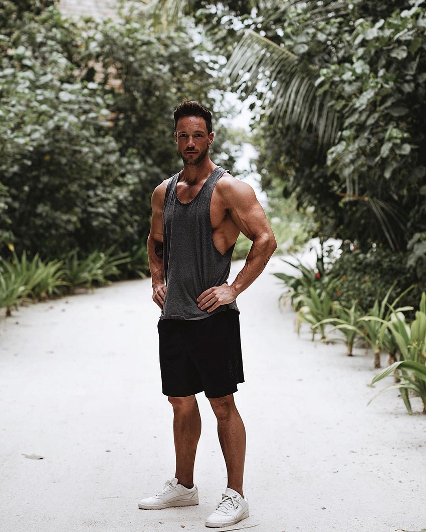 Daniel Fox standing in the nature posing for a photo looking ripped