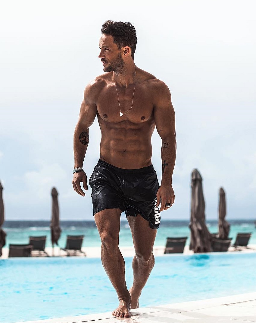 Daniel Fox walking on a beach looking ripped and strong