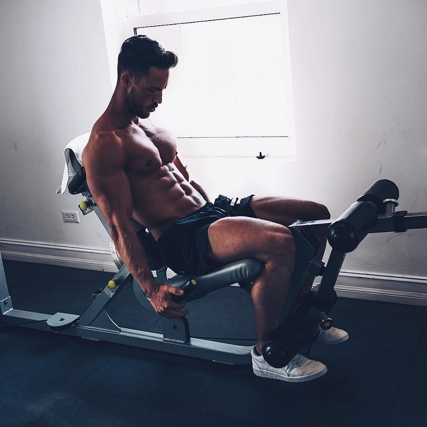 Daniel Fox doing a seated leg exercise while shirtless, looking ripped