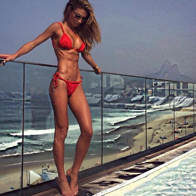 Diana Villas Boas posing outdoors wearing a red bikini, looking fit and ripped