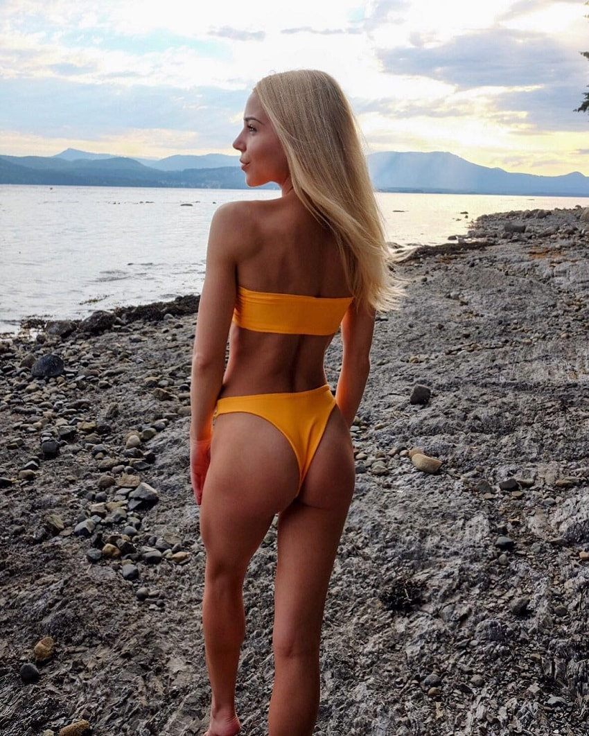 Emma Troupe posing for a photo in nature showing off her curvy glutes