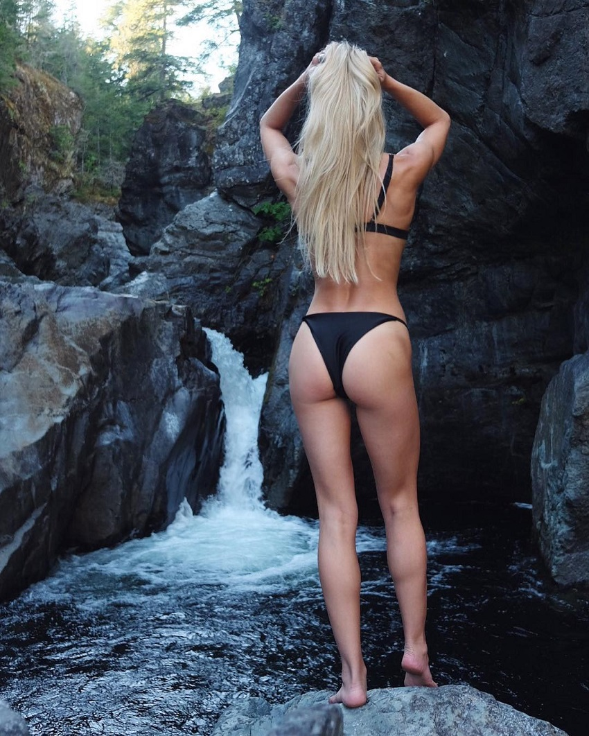 Emma Troupe standing by a waterfall looking fit and toned