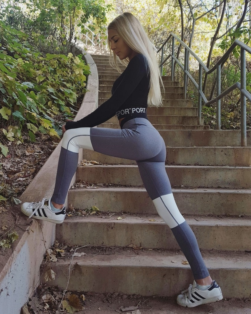 Emma Troupe posing in grey leggings outdoors looking fit