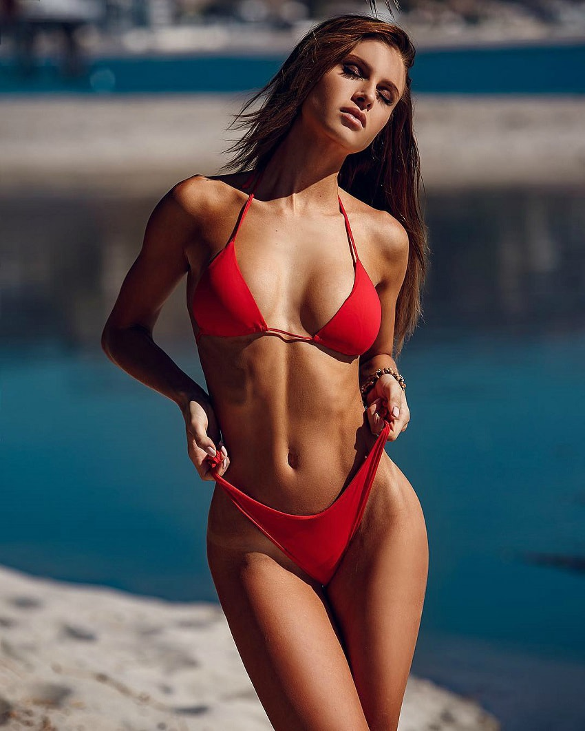 Josefine Forsberg posing for a photo in a red bikini looking fit and lean