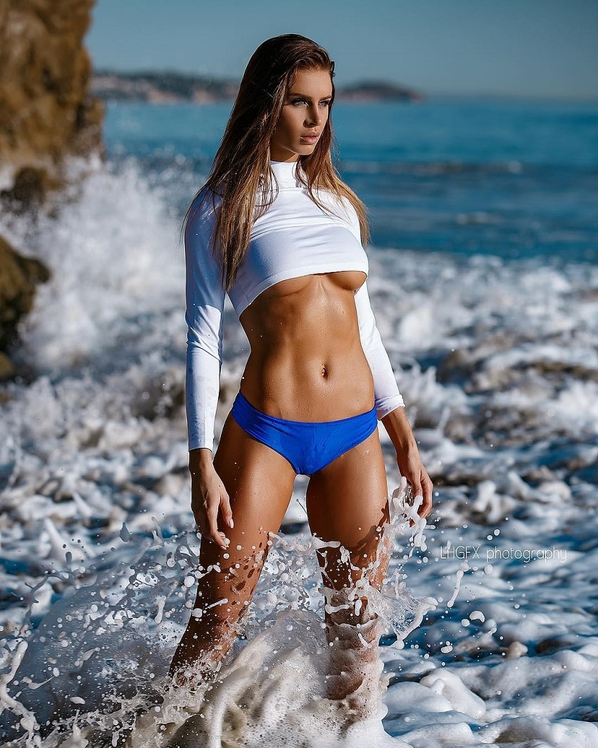 Josefine Forsberg posing on the beach showcasing her lean midsection